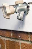 stock photo of spigot  - A Leaky Spigot on the outside of a house - JPG