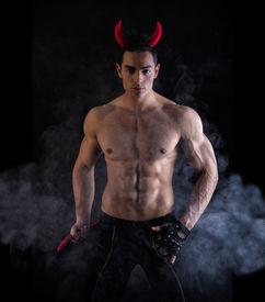 stock photo of underworld  - Sexy Handsome Man Wearing Devilish Horn Accessories Showing Muscled Body - JPG