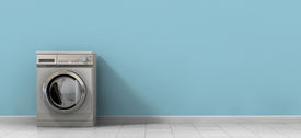 foto of laundromat  - A front view of an empty regular brushed metal washing machine in an empty room with a shiny tiled floor and a baby blue wall - JPG