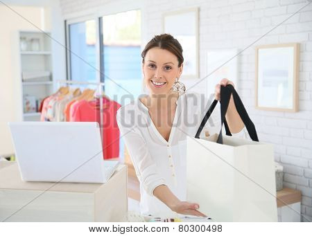 Seller in clothing store giving bag to customer