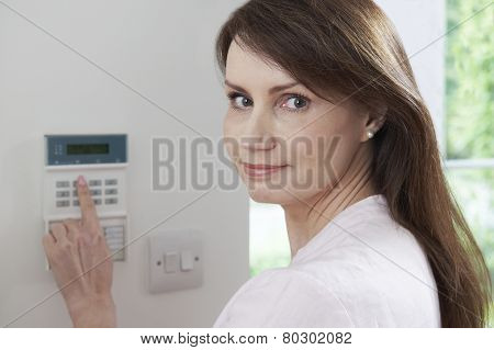 Woman Setting Control Panel On Home Security System