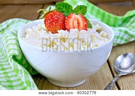 Curd with strawberries in white bowl on board