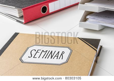 A brown folder with the label Seminar