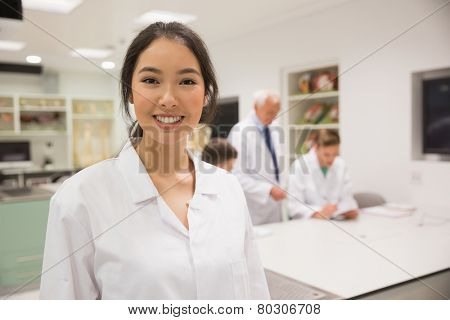 Pretty science student smiling at camera at the university