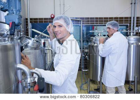 Scientist working and smiling at camera in the factory