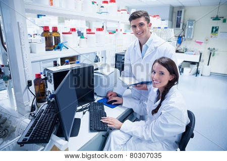 Chemist team working together at desk using computer in the laboratory