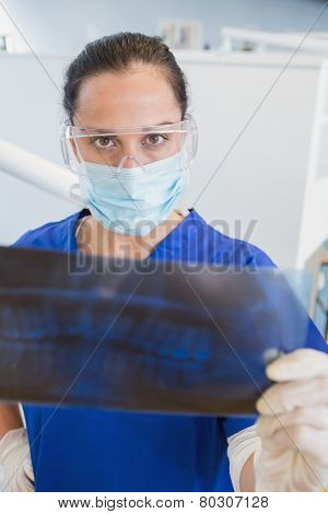Dentist wearing surgical mask and safety glasses studying the x-ray