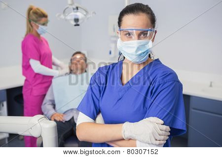 Dentist wearing surgical mask and safety glasses arms crossed behind her patient in dental clinic