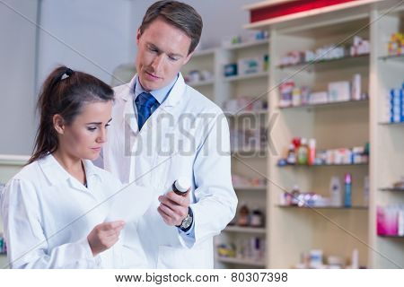 Pharmacist showing medication to his trainee in the pharmacy