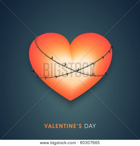 Shiny heart tied by barbed wire on blue background for Valentines Day.