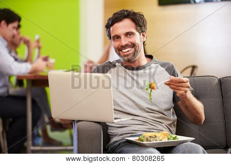 Man Sitting On Sofa And Eating Lunch In Design Studio