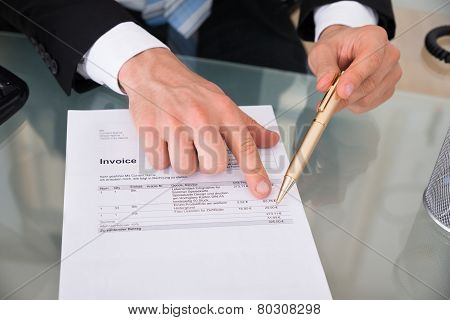 Businessman's Hands Pointing At Invoice
