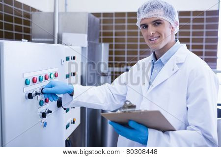 Smiling biologist using the machine in the factory