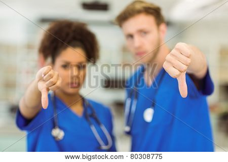 Young medical students showing thumbs down at the university