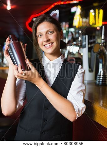Happy barmaid smiling at camera making cocktail in a bar
