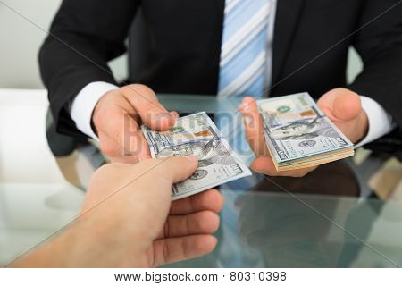 Businessman Passing Money To Colleague At Table