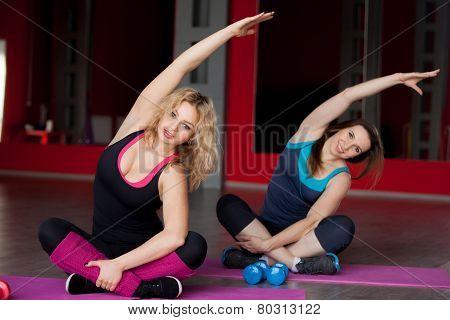 Two Pretty Girls Do Body Bending On Mats In Fitness Center