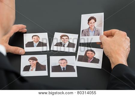 Businessman Holding Photograph Of A Candidate