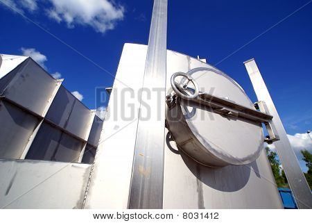 Industrial Zone, Steel Pipelines And Valve On Blue Sky