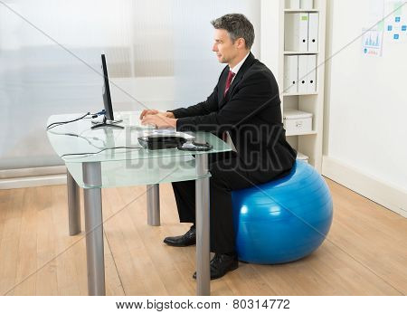Businessman Using Computer While Sitting On Pilates Ball