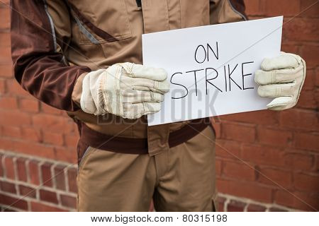 Worker Holding Placard With The Text On Strike