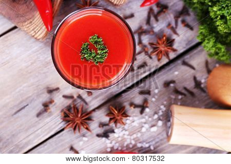 Tomato juice in glass and fresh vegetables on cutting board on wooden background