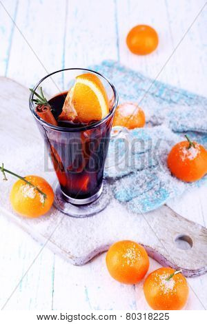 Glass of hot mulled wine with piece of orange, tangerines and mittens on cutting board and color wooden table background
