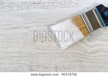 Wet Paint Brush Ready To Apply Paint On Old Boards