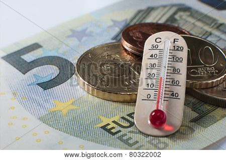 Five Euro Banknote With Some Coins And A Thermometer