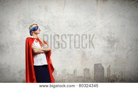 Young confident woman in red cape and mask