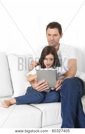 Young Father Sitting On Couch With Sweet Little Daughter Using Digital Tablet Smiling Happy