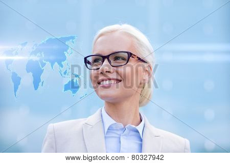 business, people and education concept - young smiling businesswoman with world map hologram outdoors