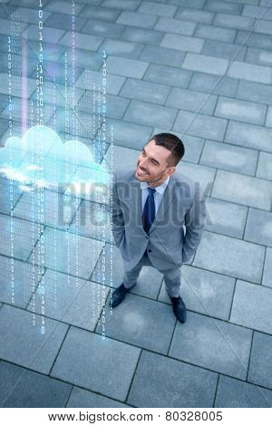 business, technology, progress, computing and people concept - young smiling businessman with cloud and binary code hologram outdoors from top