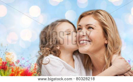 people, happiness, love, family and motherhood concept - happy daughter hugging and kissing her mother over blue lights and poppy field background