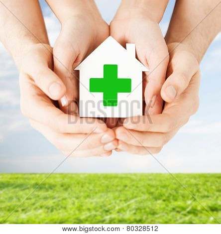 care, help, charity and people concept - close up of hands holding white paper house with green cross sign over blue sky and grass background