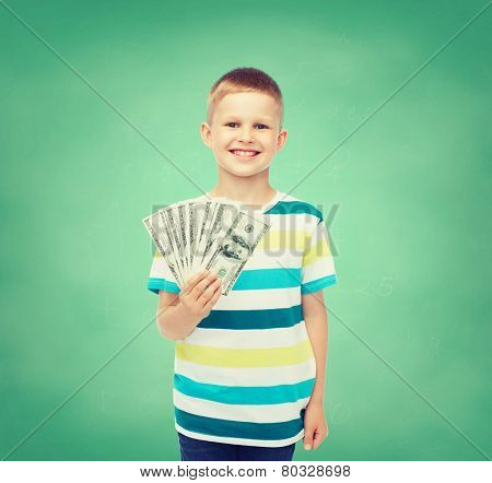 financial, planning, childhood and educational concept - smiling boy holding dollar cash money in his hand over green board background