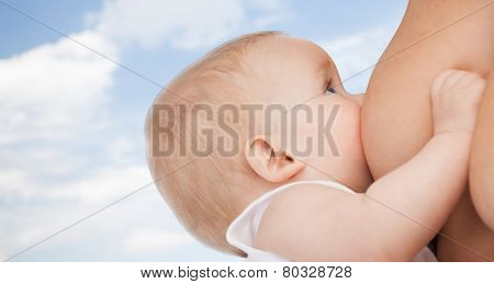 motherhood, children, people and care concept - close up of mother breast feeding adorable baby over blue sky background