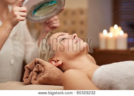 people, beauty, spa, healthy lifestyle and relaxation concept - close up of beautiful young woman lying with closed eyes and cosmetologist looking through magnifying lamp in spa