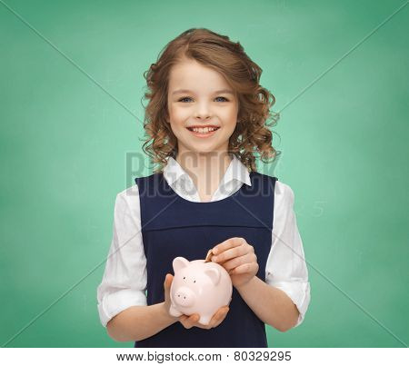people, money, savings, investments and children concept - smiling school girl putting coin into piggy bank over green chalk board lights background