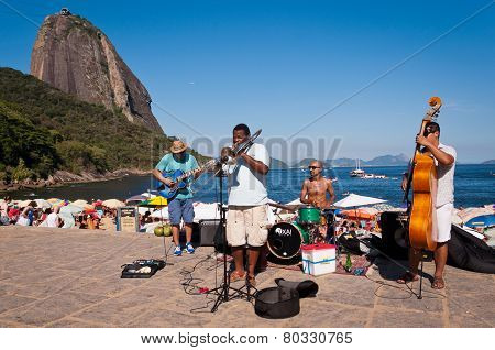 Local street band performs in the front of the beach with Sugarloaf Mountain in the background