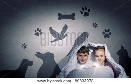 Children sitting in bed under blanket with flashlights