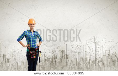 Young woman builder in hardhat wearing toolbelt
