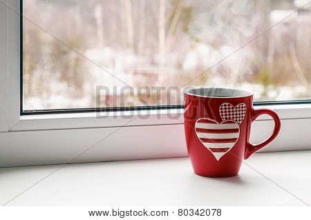 Cup With Hearts Stands On A Window