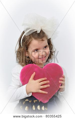 Young girl holding a plush pink heart