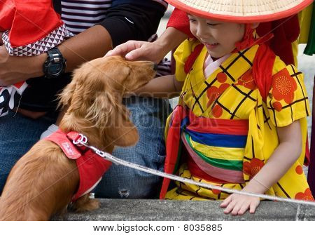 Young Japanese girl in yukata kimono plays with a dog