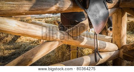 Leather horse saddle displayed on wooden fence
