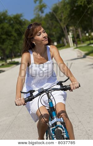 Beautiful Woman Cycling In White Sun Dress