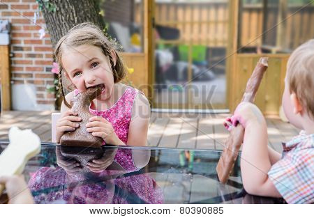 Little Girl Taking A Bite Out Of A Chocolate Bunny