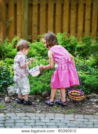 Little Boy And Girl Searching For Easter Eggs