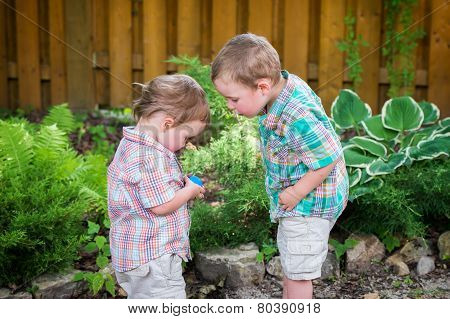Two Little Boys Looking At An Easter Egg